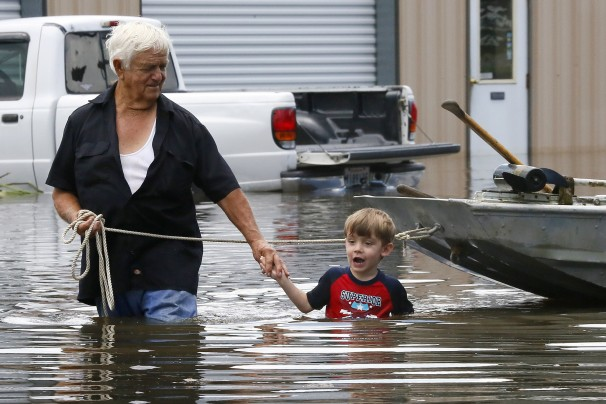man and child wading through flood water near home