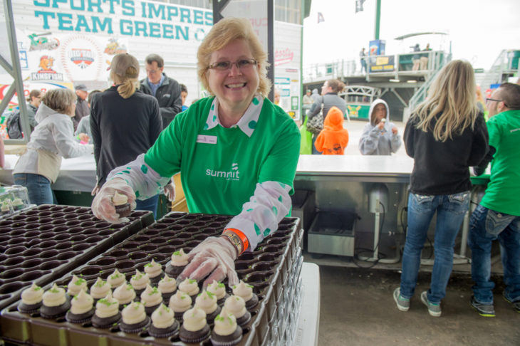 smiling woman with cupcakes