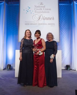 three well dressed women receiving award