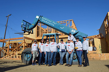 large group of people near equipment and partially built house