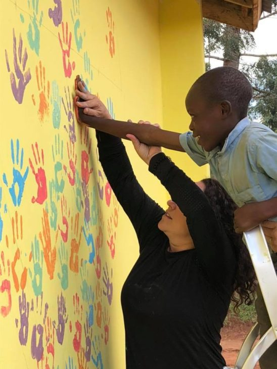 teacher helping child make hand print on mural