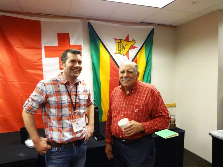 two smiling men in front of flags