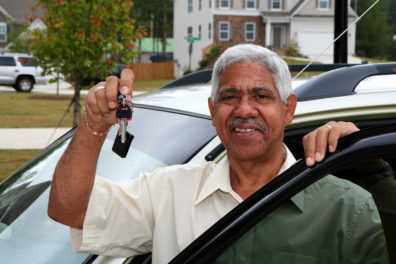 man holding up keys and standing with car door open