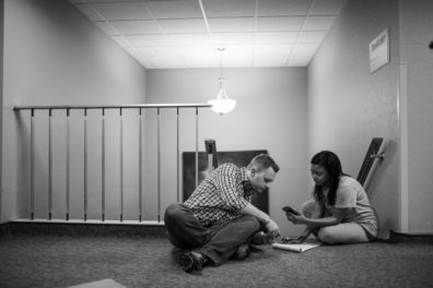 man and woman sitting on floor at top of stairs