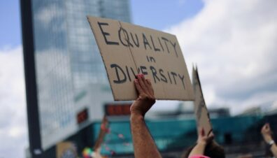 """A person holds up a sign reading """"Equity in Diversity"""" at a street proptest"""
