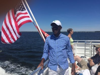 smiling man in front of flag on boat