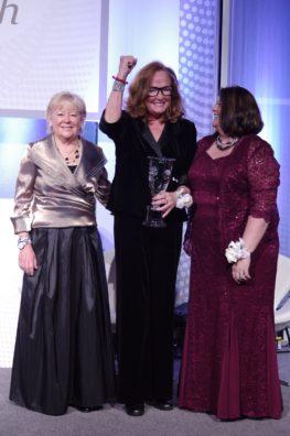 three well dressed women receiving award