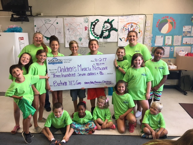 group of children with giant donation check