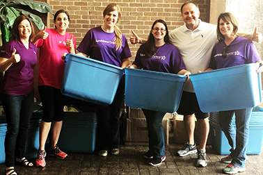 group of smiling volunteers with bin boxes