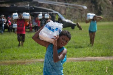 child hauling bottled water away from helicopter