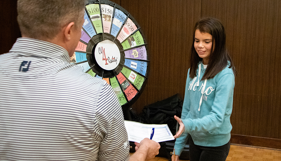 young woman besides game wheel accepts paper and pen