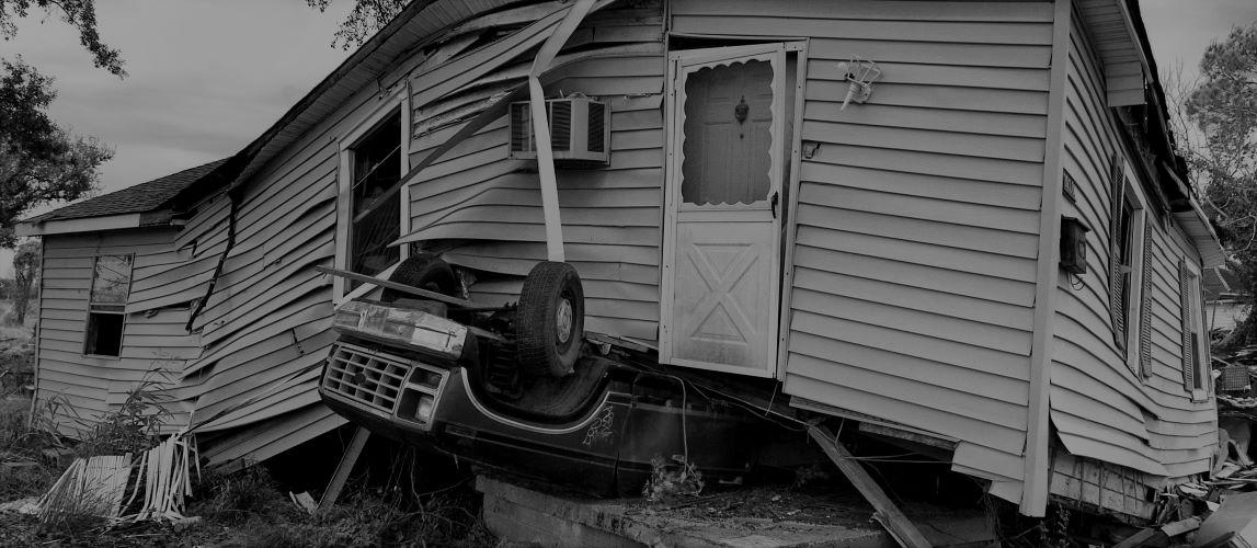 A broken house sits atop an upturned car.