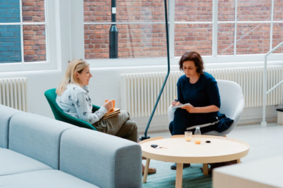 Two women discuss work at a breakout table