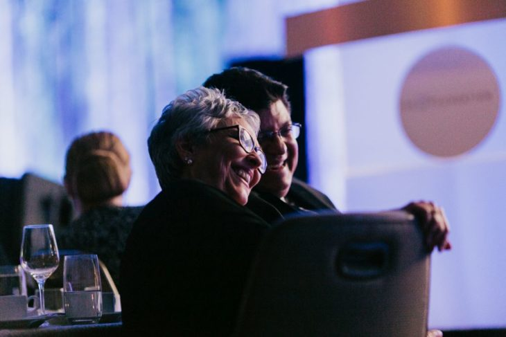 smiling couple sitting at table at awards dinner