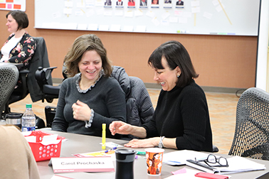 two laughing women working together at workshop