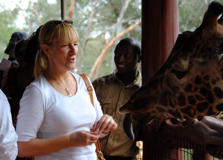 woman being approached by giraffe tongue