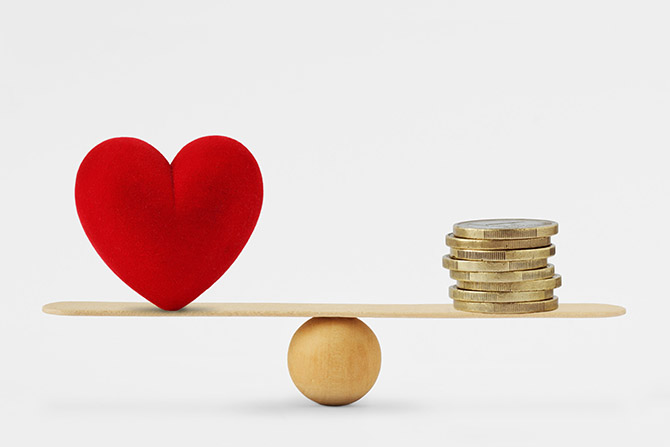 heart and money on a balance