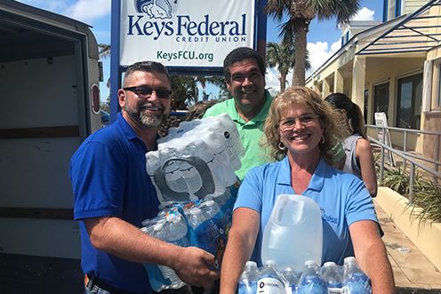 smiling group of people hauling bottled water