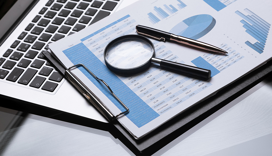 fact sheet with graphs on clipboard with magnifying glass and pen
