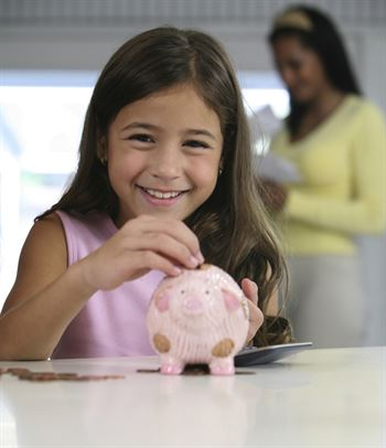 smiling child placing coins in piggy bank