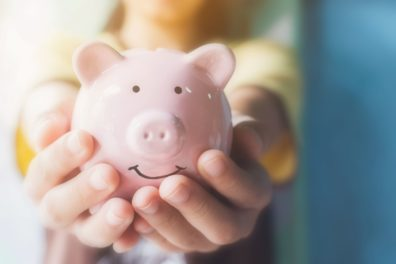 close up of hands holding piggy bank