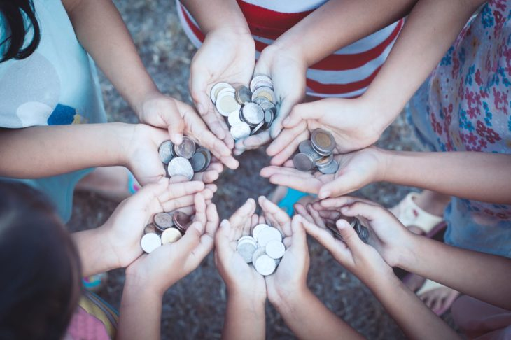 children's hands in circle full of coins