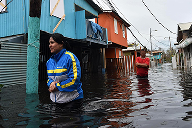 two people walking through waist high flood waters