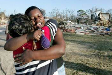 two relieved people hugging in the aftermath of a hurricane