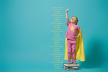 child dressed up as superhero measuring