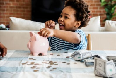 smiling child putting coins into piggy bank