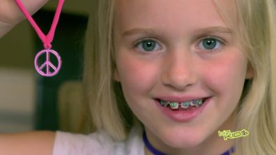 close up of blonde child with braces smiling