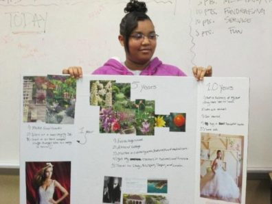 young woman holding up project