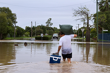 man walking with floating cooler in flood waters