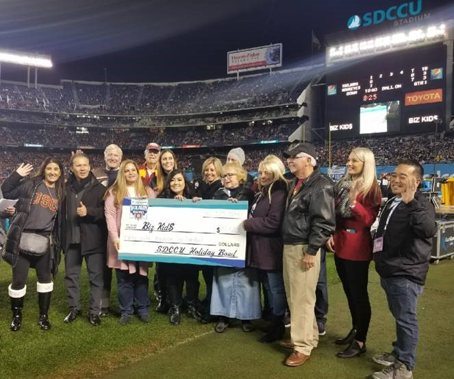 large group of people donating big check to Big Kids charity
