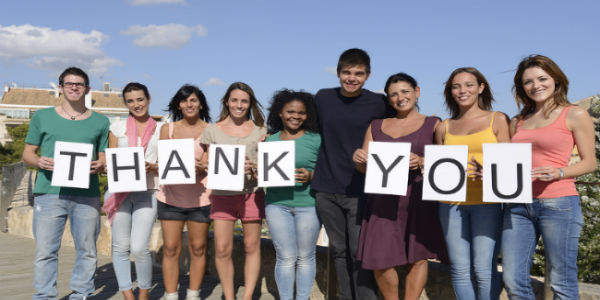 """group of people holding up letters that spell """"thank you"""""""