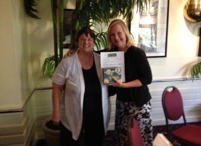 two smiling women holding up award