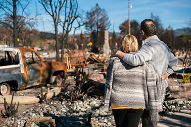 two people face the wreckage from a wildfire